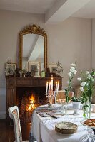 Festively set table in dining room with antique furniture and fire burning in open fireplace