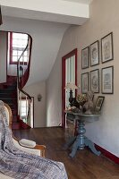 Elegant console tables and gallery of pictures in foyer of 18th-century, French country house in shades of red and grey