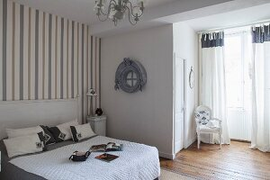 French-style, grey and white bedroom with striped wallpaper and Baroque chair