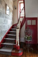 Red and grey stairwell of 18th-century, French country house with stone wall and vintage birdcage