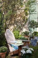 Plain wooden deckchair amongst many pots and plants in garden