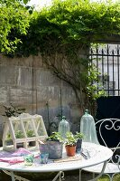 Ornate metal garden furniture with terrarium and tools on table in walled garden