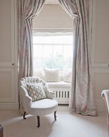White armchair in front of bay window with window seat and elegant curtains