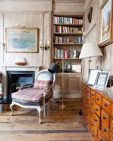 Reading area with fireplace in wood-panelled study