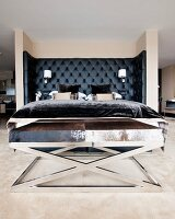 Bed with black upholstered headboard and chrome bench with animal-skin cover in masculine bedroom