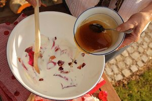 Making a milk bath with rose petals and honey