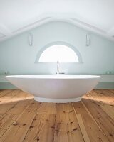 Modern, free-standing bathtub on rustic wooden floor in front of semicircular window in gable-end wall