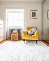 Golden-yellow armchair on white rug next to deep-set window