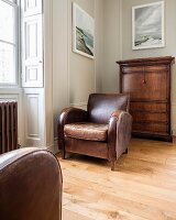 Brown, vintage leather armchair next to window in front of narrow chest of drawers against wall painted pale grey in traditional interior