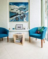 Blue fifties' armchairs flanking side table in front of artwork in narrow niche