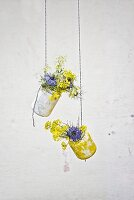 Jam jars covered in tissue paper hung from strings and used as vases