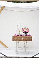 Dome-shaped arrangement of summer flowers, glass vessels & china figurine