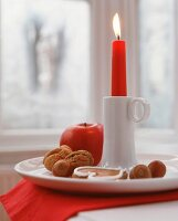 Lit red candle in white china candlestick with nuts, apples and gingerbread
