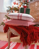 Woollen blanket, checked scatter cushions and gift on cane-back chair in front of Christmas tree