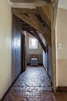 Long hallway with low ceiling and rustic stone-tiled floor