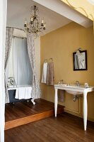 Vintage-style bathroom with yellow walls, wooden floor, washstand and free-standing bathtub on platform