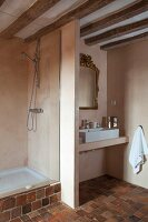Wood-beamed ceiling, stone-tiled floor and partition between sink and shower areas in rustic bathroom