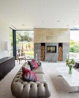 Graues Chesterfield-Sofa und Marmor-Couchtisch vor modernem Kamin mit Nischen für Holz