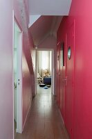 Pink wall with porthole windows in doors in narrow hallway