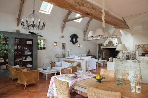 Exposed rustic wooden beams, dining area and wicker armchairs in lounge in open-plan interior
