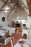 High-ceilinged interior with exposed wooden roof structure and fireplace in cosy lounge area on platform