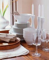 White china crockery and candlesticks on wooden table