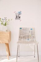 A classic bucket chair decoupaged with newspaper standing next to a wooden Scandinavian chest of drawers