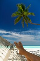 Feet of person lying in hammock under palm tree on beach in the Maldives