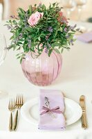 Romantic flower arrangement in glass vase and festive place settling with lilac napkin