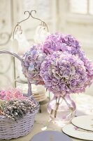Bouquet of purple hydrangeas in glass vase next to basket of dried lavender