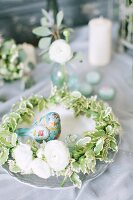 Wreath of Ficus leaves and ranunculus with bird ornament