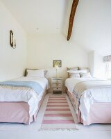 Pink and white striped rug between twin beds in rustic bedroom
