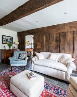 Pale ottoman, couch and armchair against rough board wall in rustic living room