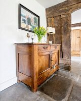 Vase of tulips on simple, wooden cabinet on old stone floor in front of open doorway in rustic board wall