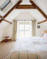 Double bed in bedroom with wood-beamed ceiling