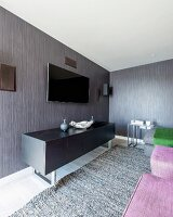 Black sideboard below flatscreen TV on grey and brown striped wallpaper in modern interior