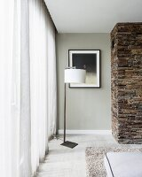 Modern standard lamp with white lampshade in corner next to floor-length curtain