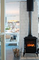Fire in vintage-style log-burner against white brick wall and view into kitchen