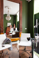 Classic chair with white leather cover behind glass table and large mirror with carved wooden frame on green-painted wall