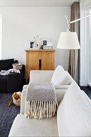 Elegante Polstercouch und Sessel in Naturweiss, darüber weisser Lampenschirm