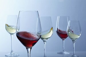 Red wine and white wine swirling in glasses