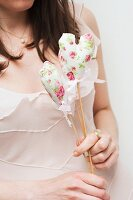 Woman holding floral, fabric love-heart on wooden stick