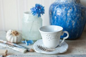 Blue, antique vase and decorated cup, paintbrushes and flower in jar
