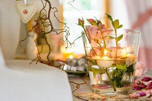 Tischdeko im Glas mit Rosen und Schwimmkerzen