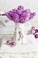 Purple hyacinths in vintage jug with baubles on lace doily
