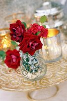 Red roses and lewisia in glass vase and tealight holders on cake stand