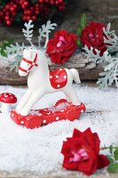 Small rocking horse and toadstool ornaments and rose arranged on artificial snow