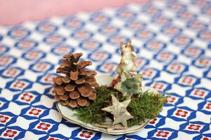Festive table decoration of pine cone, moss, star and animal ornament