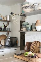 Crockery on stainless steel shelves on whitewashed wall in kitchen