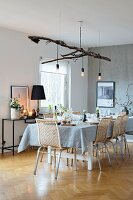Festively set Christmas dining table with Scandinavian cane chairs and lights suspended from branch